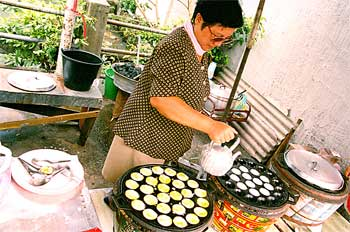 Mujer thai preparando dulces de leche de coco, Tailandia