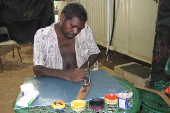 Artesano aborigen pintando un boomerang, Australia