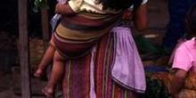 Mujer con niño a la espalda en el mercado de Antigua, Guatemala