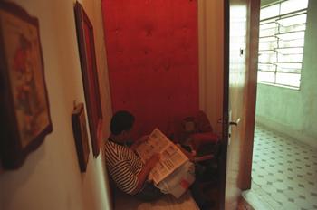 Hombre leyendo un periódico, favela de Sao Paulo, Brasil