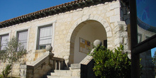 Fachada de piedra con arco y escalera en Cabanillas de la Sierra