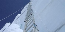 Escalera suspendida contra la pared de hielo con cuerdas