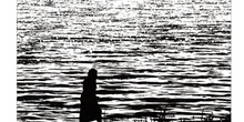 Silueta de una mujer caminando por un ribera