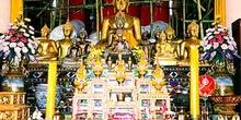 Altar budista decorado con imágenes de budas, presentes y velas,