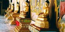 Budas dorados con frescos con escenas sagradas de fondo, Tailand