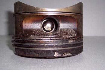 Pistón de un motor completo corroído y erosionado