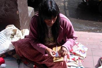 Mujer sentada realizando un trabajo artesanal