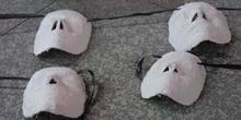 Cuatro máscaras blancas sobre el suelo