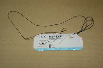 Seda de sutura con aguja curva