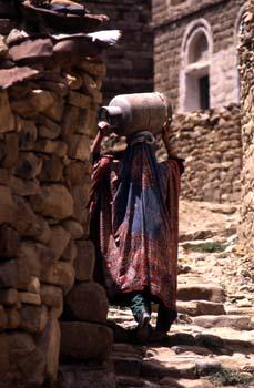 Mujer llevando una botella de gas sobre la cabeza, Yemen