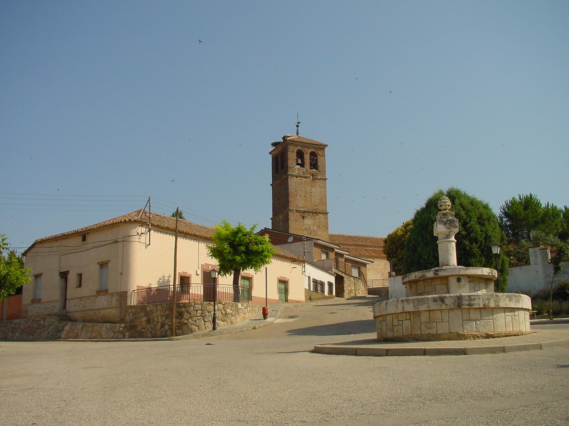 Plaza con fuente e iglesia al fondo en Ribatejada