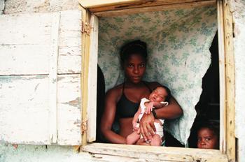 Mujer enseña su bebé recién nacido, favelas de Rio de Janeiro, B