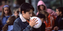 Niño inflando un globo