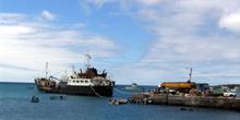 Barco de mercancías descargando en el muelle del Puerto Baqueriz