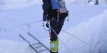 Escalador cruzando una grieta en un glaciar con una escalera