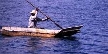 Hombre remando en una barca de fondo plano en el lago Atitlán, G
