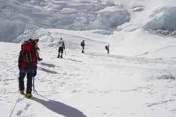 Fila de escaladores escalando a lo largo de una cuerda fija