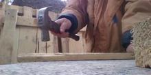 Quitando los clavos a las tablas de los pallet