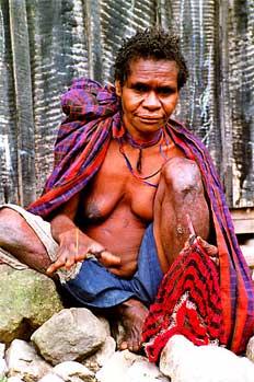 Mujer tejiendo tradicional bolsa de transporte, Irian Jaya, Indo